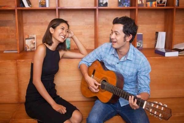 homme jouant de la guitare et souriant